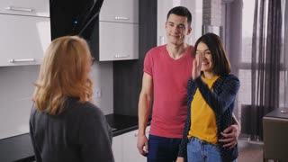 Young excited couple ready to get their new home keys from female real-estate agent. Sweet smiling owner standing with her husband, catching key and shaking hands with professional realtor.