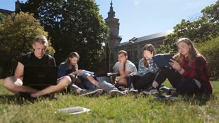 Young exhausted students learning on campus lawn