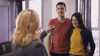 Young happy couple getting keys to their new apartment. Back view of female real-estate manager giving the key to excited brunette wife. Happy family hugging and laughing together from happiness.