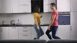 Young happy couple of hipster newlyweds dancing together indoors. Funny creative young people making dance moves and laughing in the kitchen at home. Slow motion.
