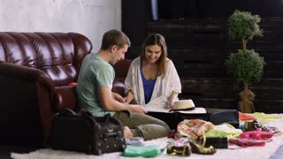 Young happy couple planning travel with map