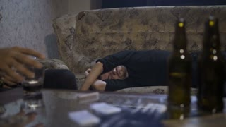 Young male drug addict lying on the sofa, unconscious overdosed. Cocaine, alcohol glass, rolled-up dollar bills, empty beer bottles on table. Male hand taking glass of alcohol from table. Dolly shot
