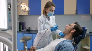 Young male patient in dental chair receiving tooth decay treatment for cavities in dental office. Female dentist in lab coat, gloves and face mask holding drill machine and starts dental treatment