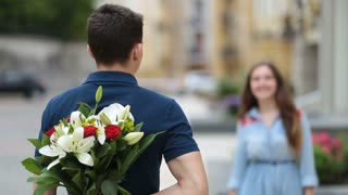 Young man hiding flowers for girl behind his back