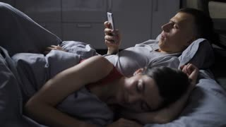 Young mid adult couple lying in bed at night under blanket. Young wife sleeping, while her handsome husband texting and cheating on her online via mobile phone.
