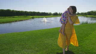 Young mother in yellow dress walking barefoot on grass near pond embracing and carrying little toddler daughter with down syndrome in arms. Sunny girl and mother enjoying summer outdoors. Steadicam
