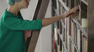 Young student looking for books on the shelves