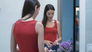 Young woman standing in front of the bathroom mirror looking at pregnancy test result upset and disappointed. Anxious female learned pregnancy result