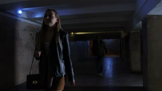Young woman walking alone in subway tunnel at night. Male thief in hoodie runs and steals bag from female. Sad, angry and frustrated woman standing in shock. Steadicam stabilized shot
