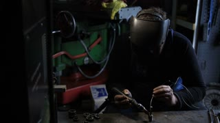Welder man Tig welding in workshop