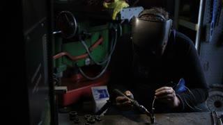 Welder man Tig welding in workshop