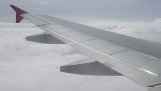 Wing of airplane flying above the clouds in sky