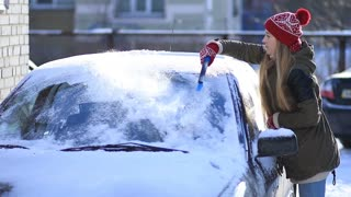 Woman cleaning snow from car roof using brush