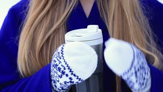 Woman drinking hot wine from thermocup in winter