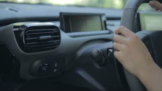 Woman driving car and using turn signal switch