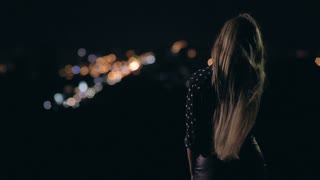 Woman enjoying night city from observation deck