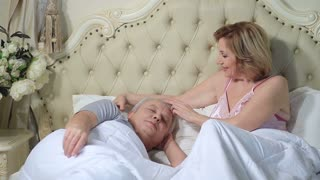 Woman gently waking up man in the morning