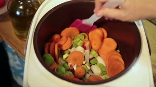 Woman hands stirring vegetables in Multicooker