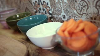 Woman putting chopped onion in ceramic bowl