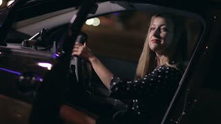 Woman sitting in car making dance moves at night
