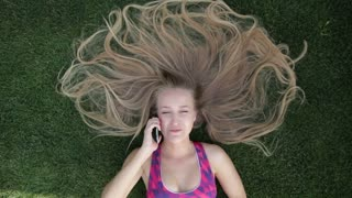 Woman with blonde amazing long hair lying on grass