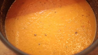 Woman's hand adding salt and spices into soup