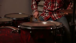 Young drummer playing at drum set