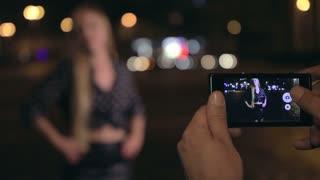 Young man makes photos of his girlfriend at night