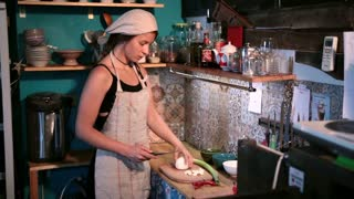 Young woman chopping onion on wooden cutting board