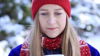 Young woman enjoying scent of coffee in wintertime