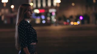 Young woman walking through a night city street