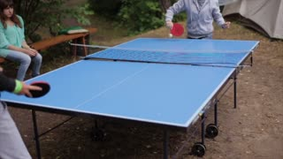 People playing table tennis outdoors.
