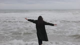 A beautiful barefooted girl in warm clothes runs towards the sea on a cold day, gets afraid of the cold water, and runs back