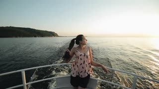 A beautiful brown-haired girl with a ponytail stands on a cruise ships bow looking to the side. Turning around and looking at nature