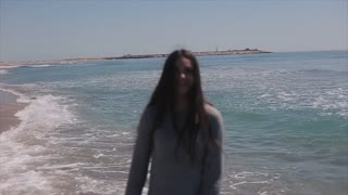 A beautiful girl in a dress walking backwards along the beach. Slow motion