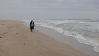 A beautiful girl running along the sandy beach on a cool spring day