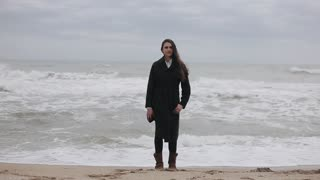 A beautiful girl standing on the beach on a cold windy day