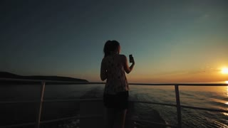 A beautiful girl with long hair takes a photo of herself on her smartphone in front of the river, hills, and the sky at twilight