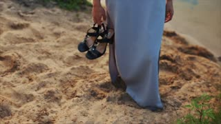 A beautiful woman wearing an evening dress walking barefoot on the beach, holding shoes. Slow motion. Feet on the sand