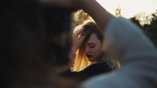 A close-up of a photographer shooting a beautiful blond girl outside
