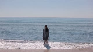 A full-length shot of a beautiful girl in a short wet dress standing in the sea