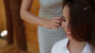 A hairstylist fixing hair of a beautiful young girl. The model is smiling and laughing. Before the wedding. A close up view