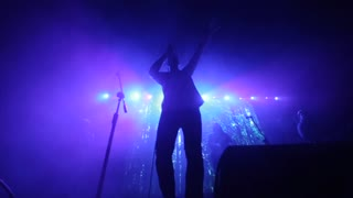 A man with a band singing on the stage. A fast song. Purple lights. Smoke