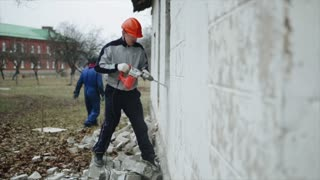 A man with a perforator breaking a wall outside. A man in a protective helmet. Demolition work
