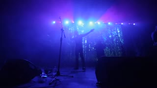A man with two lifted up hands performing at a concert. Blue light. Rock band. The woman jumping at the background