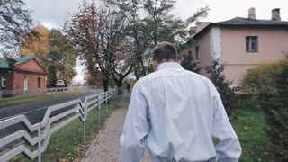 A young business man walking down the street. Autumn. From back perspective.