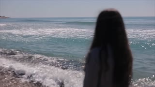 Back half-body view of a beautiful girl looking at the sea
