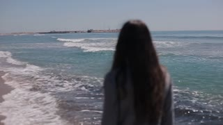 Back half-length view of a girl with long loose dark hair walking in water on the beach. Slow motion