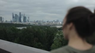 Back view of a beautiful girl looking at the city. Cityscape. The girl lets her brown long hair down
