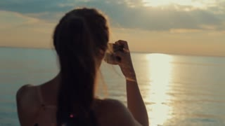 Back view of a beautiful girl taking a picture of the river at sunset. Taking photos on smartphone